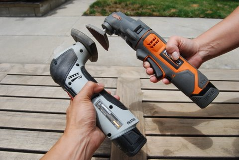 A carpenter shows his cordless oscillating tools of choice in comparison by holding them close together