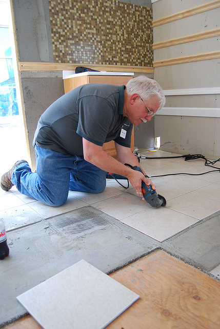 A man is working on floor tile removal by moving his oscillating tool across tile grout